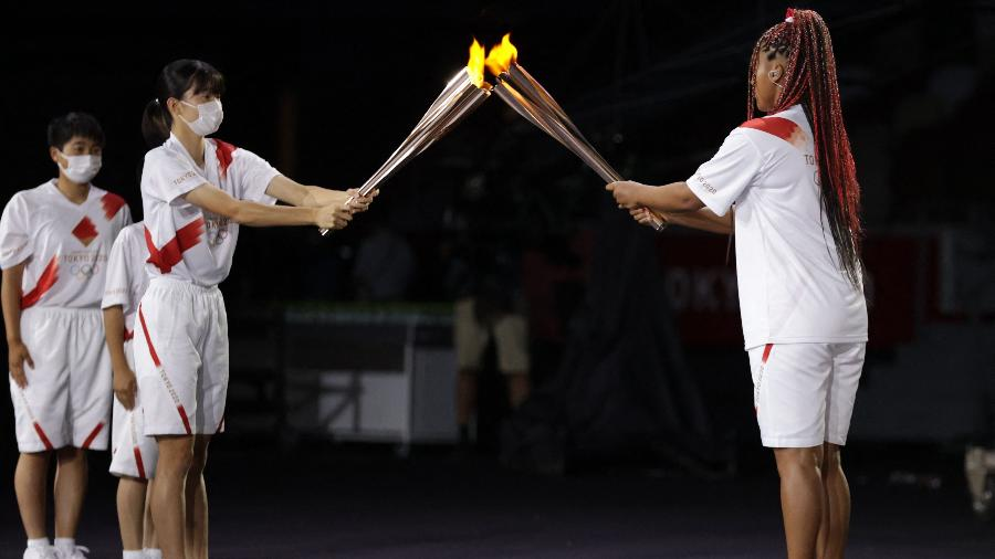 A chama foi entregue a tenista Naomi Osaka por crianças que participaram da cerimônia de abertura - HANNAH MCKAY/POOL /AFP