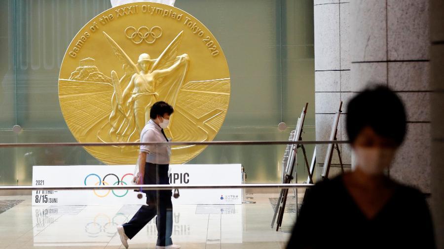 Mulheres de máscara andam próximas a uma reprodução em grande escala da medalha das Olimpíadas de Tóquio - REUTERS/Kim Kyung-Hoon