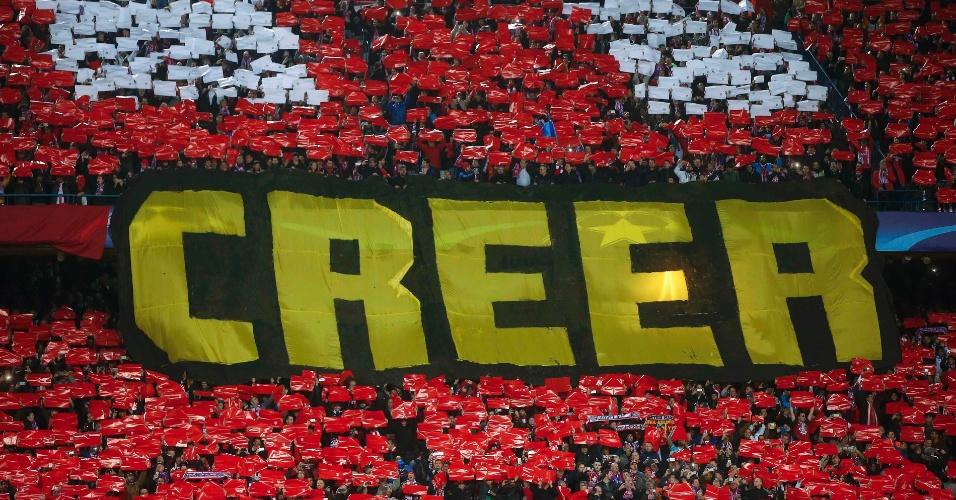 """Torcida do Atlético de Madri, antes da partida contra o PSV, estende bandeira com a palavra """"creer"""" (acreditar, em espanhol)"""
