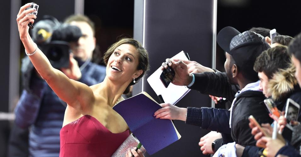 A meio-campista Carli Lloyd dá autógrafos e posa para selfies antes de entrar no local da premiação, em Zurique