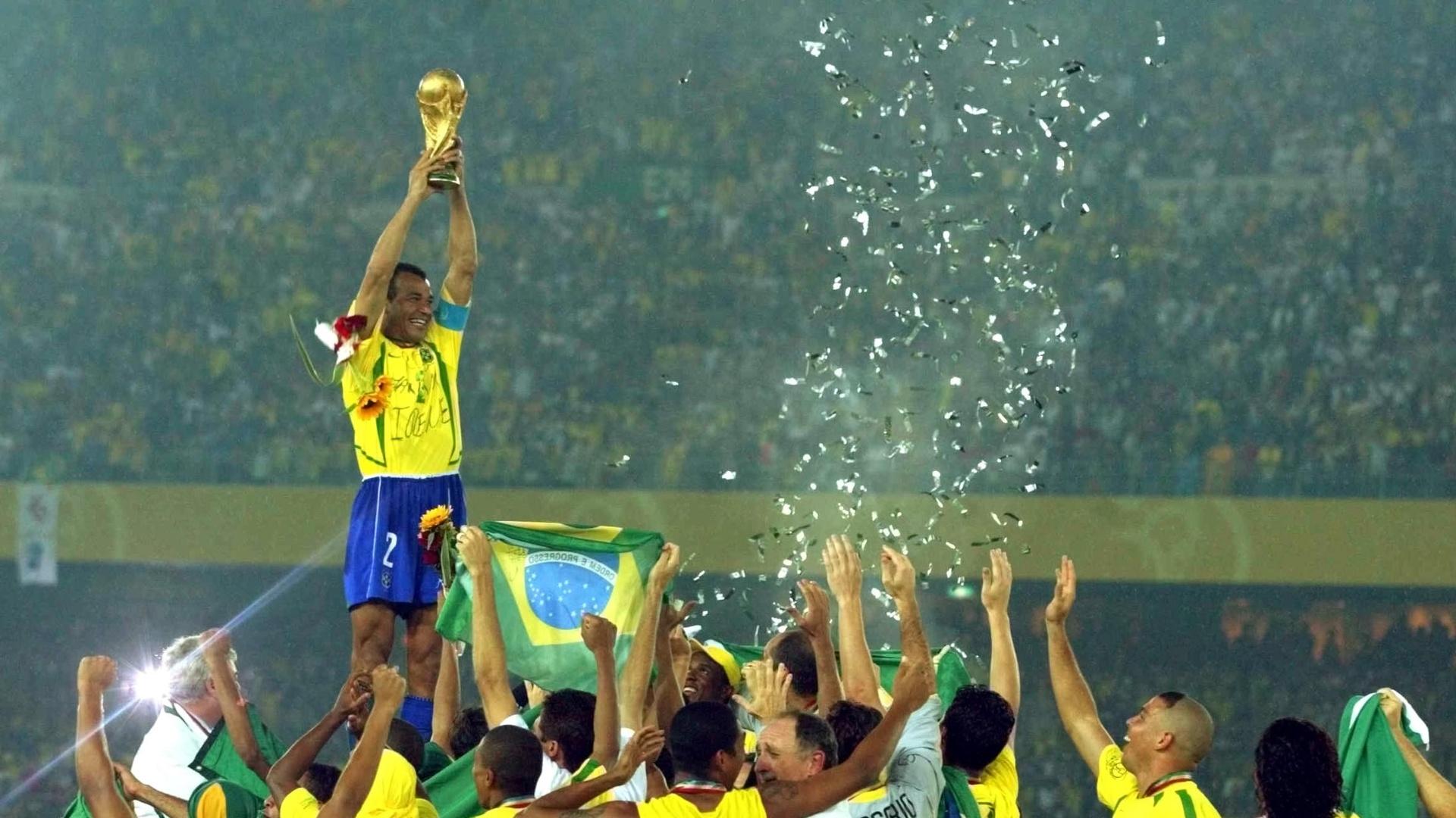 Cafu ergue a taça da Copa do Mundo de 2002 sob olhares de companheiros e comissão técnica da seleção