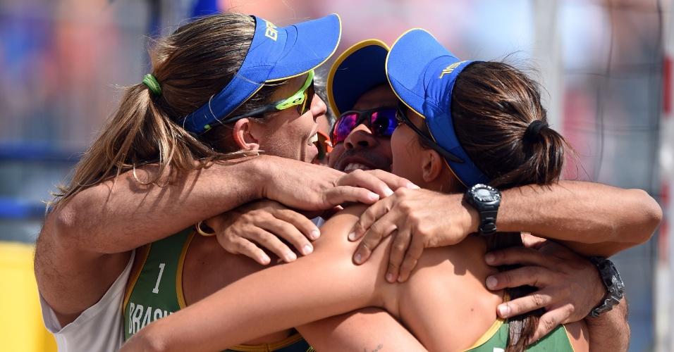 Carol e Lili comemoram com o técnico a vitória sobre as canadenses Melissa Humana-Paredes e Taylor Pischke