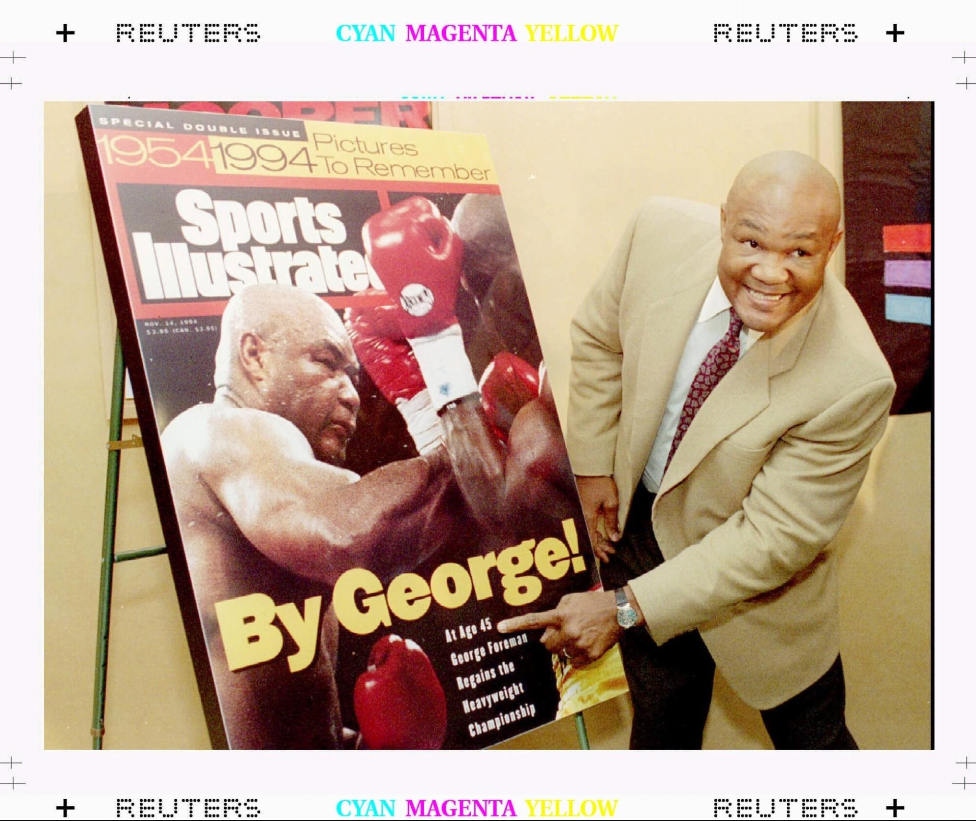 O campeão mundial de boxe dos pesos pesados George Foreman mostra um cartaz da revista Sports Illustrated