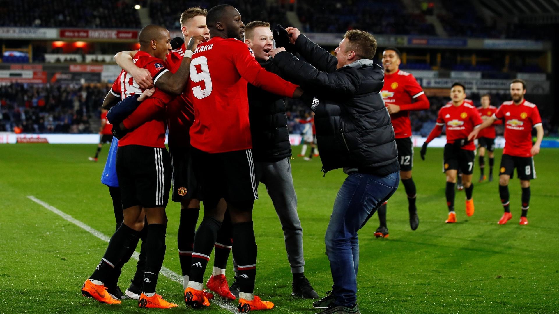 Torcedores invadem o gramado e comemoram junto com os jogadores do Manchester United