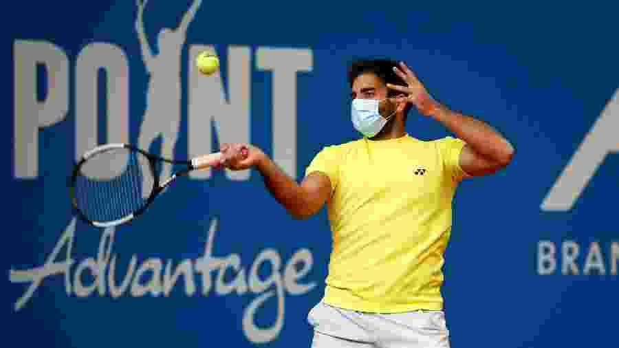 2.mai.2020 - O tenista alemão Benjamin Hassan usa uma máscara facial enquanto se aquece para uma partida de tênis - Wolfgang Rattay/REUTERS