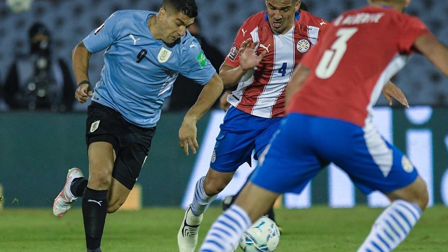 Suárez e Balbuena disputam a bola em jogo entre Uruguai e Paraguai, pelas Eliminatórias da Copa - SANDRO PEREYRA/AFP