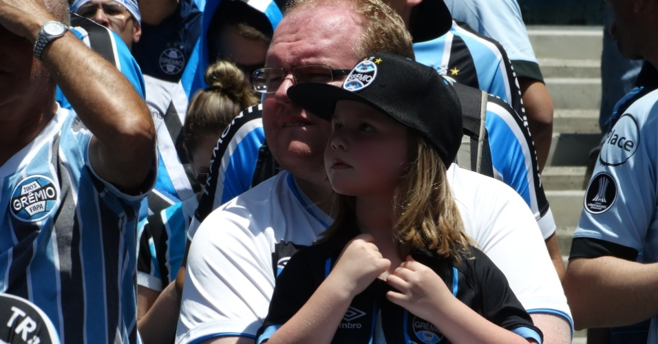 Torcedores do Grêmio aguardam a chegada do time na Arena no sol de Porto Alegre