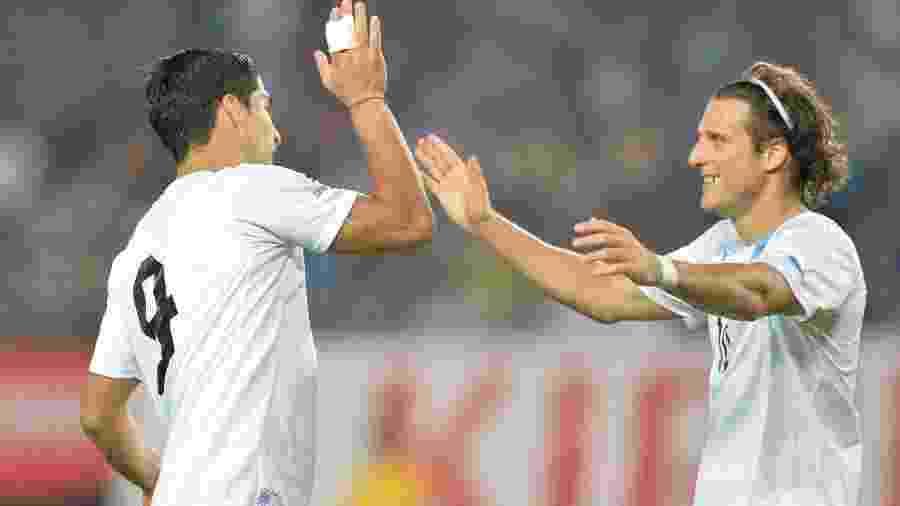 Luis Suarez comemora gol pela seleção uruguaia com Diego Forlan em jogo contra o Japão -  AFP PHOTO / KAZUHIRO NOGI