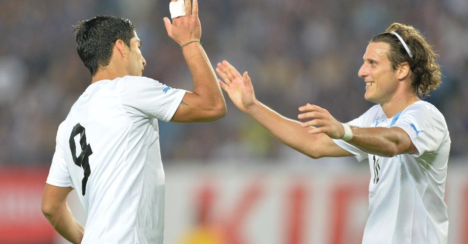Luis Suarez comemora gol pela seleção uruguaia com Diego Forlan em jogo contra o Japão