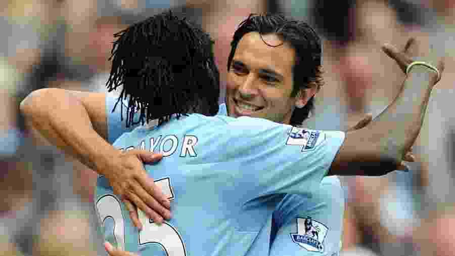 Roque Santa Cruz e Emmanuel Adebayor se abraçam durante partida do Manchester City - Reprodução