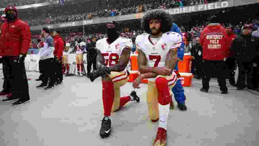 Colin Kaepernick (dir) e Eli Harold ajoelham na hora da execução do hino dos EUA no jogo entre San Francisco 49ers e Chicago Bears na NFL em 2018 - Michael Zagaris/San Francisco 49ers/Getty Images