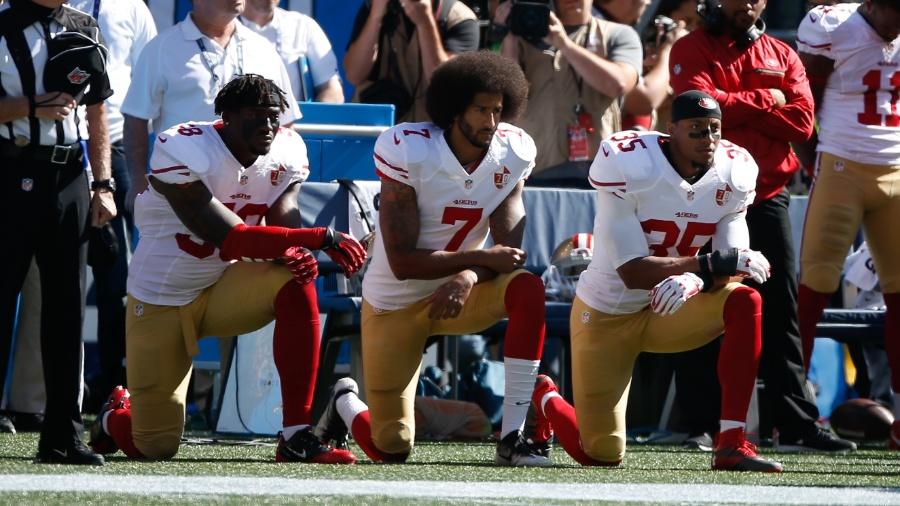 Colin Kaepernick, ex-quarterback do San Francisco 49ers, se ajoelha durante a execução do hino americano -  Otto Greule Jr/Getty Images