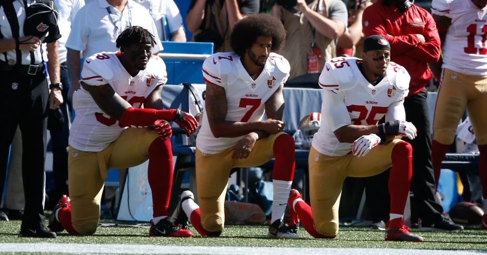 Colin Kaepernick, quarterback do San Francisco 49ers, se ajoelha durante a execução do hino americano