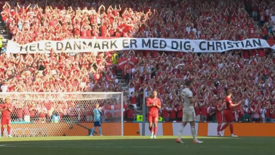 Faixas de apoio ao meia foram exibidas pela torcida dinamarquesa; jogo ficou paralisado por um minuto - Reprodução/SporTV