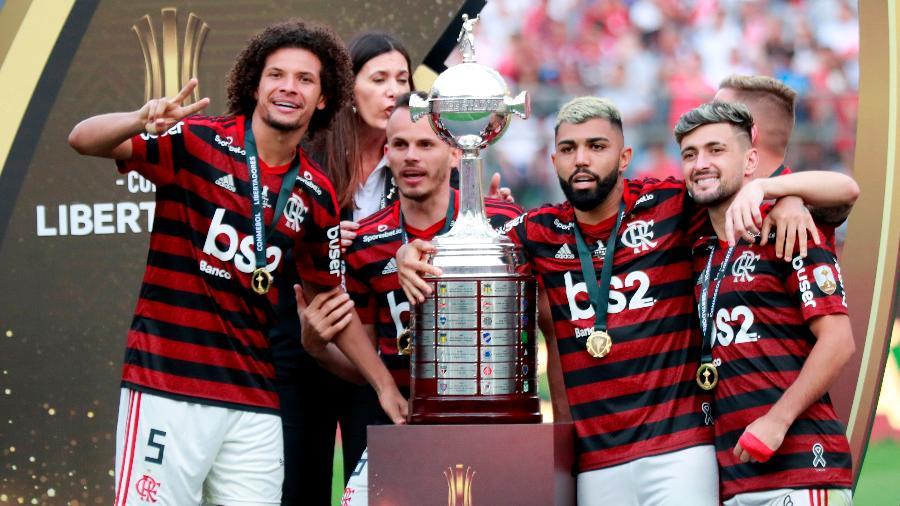 Arrascaeta, Arão e Gabigol comemoram título ao lado da taça - Henry Romero/Reuters