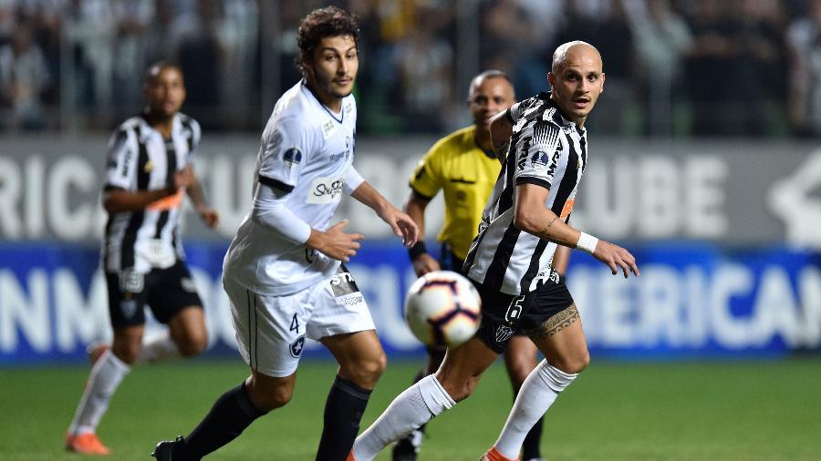 Fabio Santos, do Atlético-MG em disputa de bola com Marcinho, do Botafogo, durante partida pela Copa Sul-Americana - DOUGLAS MAGNO / AFP