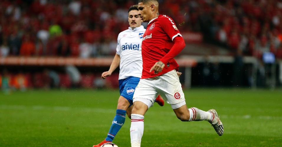 Gabriel Neves, do Nacional (URU), disputa lance com Paolo Guerrero, do Internacional, durante partida pela Libertadores