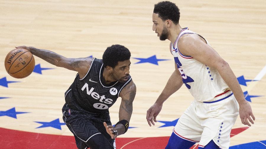 Kyrie Irving, do Brooklyn Nets, encara a marcação de Ben Simmons, do Philadelphia 76ers, em jogo da NBA - Mitchell Leff/Getty Images/AFP