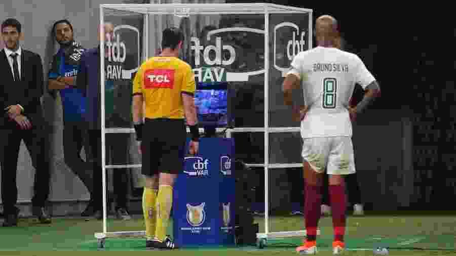 Raphael Claus consulta o VAR durante a partida entre Grêmio e Fluminense - RICHARD DUCKER/FRAMEPHOTO/FRAMEPHOTO/ESTADÃO CONTEÚDO