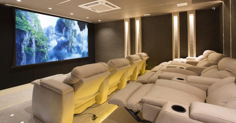Outro ambiente que se destaca na casa é a sala de cinema. No cômodo, foram colocadas poltronas espaçosas e utilizados tons escuros na parede para dar um clima mais intimista com cara de cinema