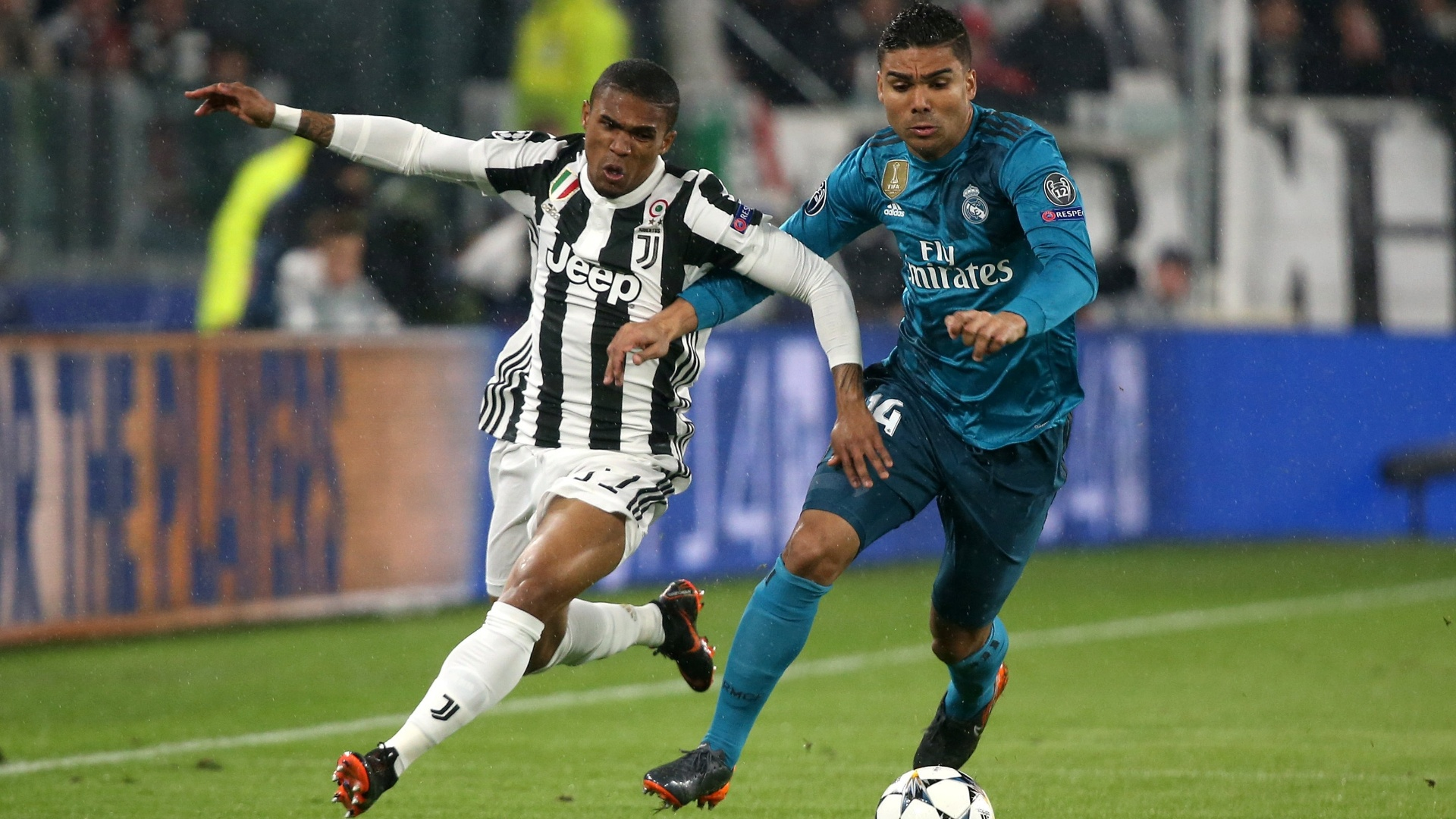 Douglas Costa e Casemiro disputam a bola no jogo entre Juventus e Real Madrid