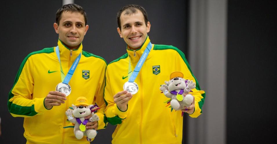 Daniel Paiola e Hugo Arthuso exibem as medalhas de prata conquistadas no badminton