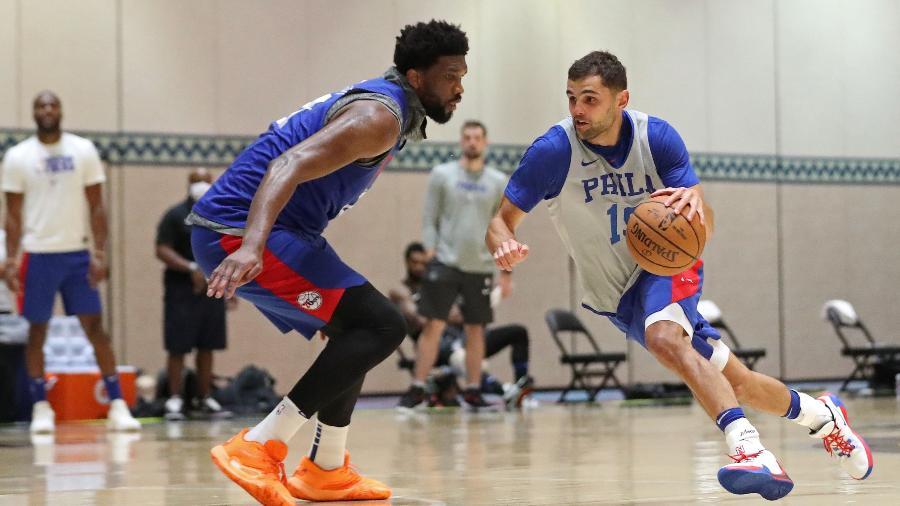 """Raulzinho (direita) em treino pelo Philadelphia 76ers na """"bolha"""" da NBA na Disney, em Orlando - Joe Murphy/NBAE via Getty ImagesJoe Murphy/NBAE via Getty Images"""