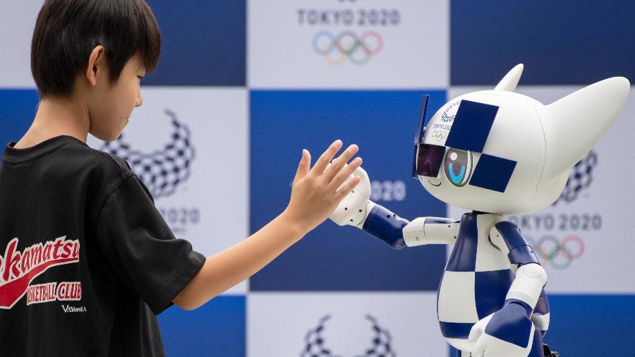 O robô mascote Miraitowa, das Olimpíadas de Tóquio, cumprimenta garoto durante apresentação para a imprensa - NurPhoto/NurPhoto via Getty Images
