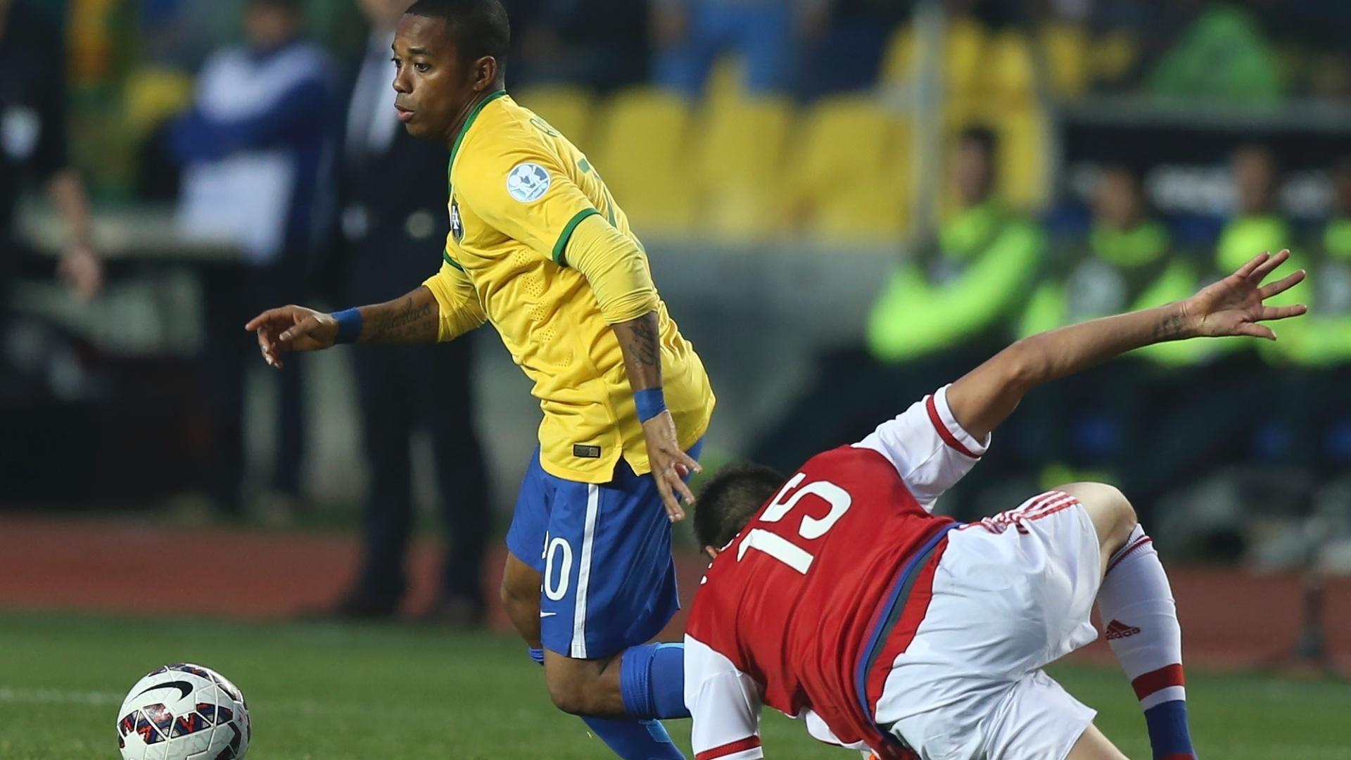 Robinho tenta fugir da marcação do jogador paraguaio em jogo do Brasil na Copa América