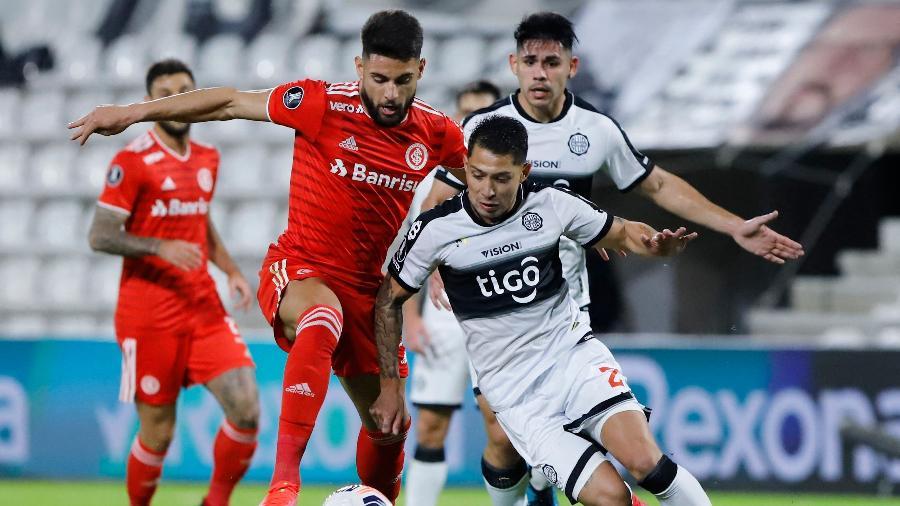 Victor Salazar, do Olimpia, disputa a bola com Yuri Alberto, em jogo válido pelas oitavas de final da Libertadores - NATHALIA AGUILAR/AFP