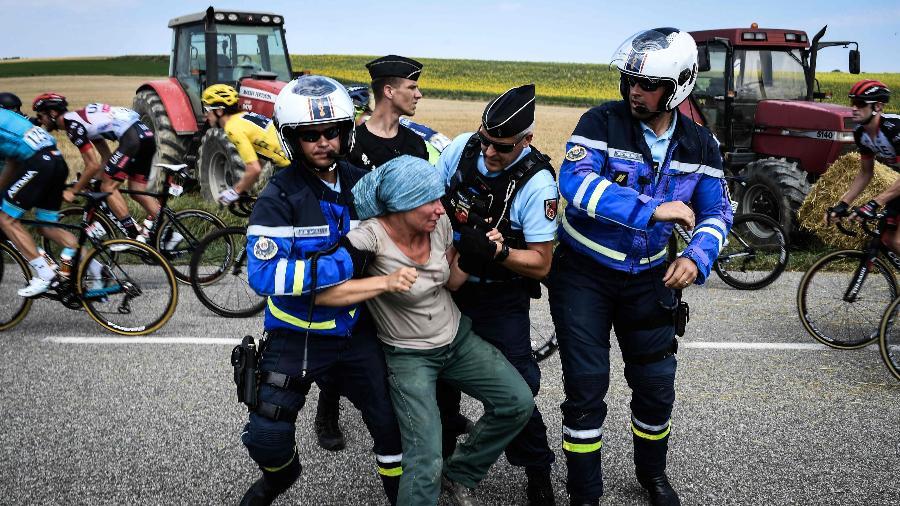Agricultores são retirados pela polícia de pista durante Volta da França - AFP PHOTO / Jeff PACHOUD