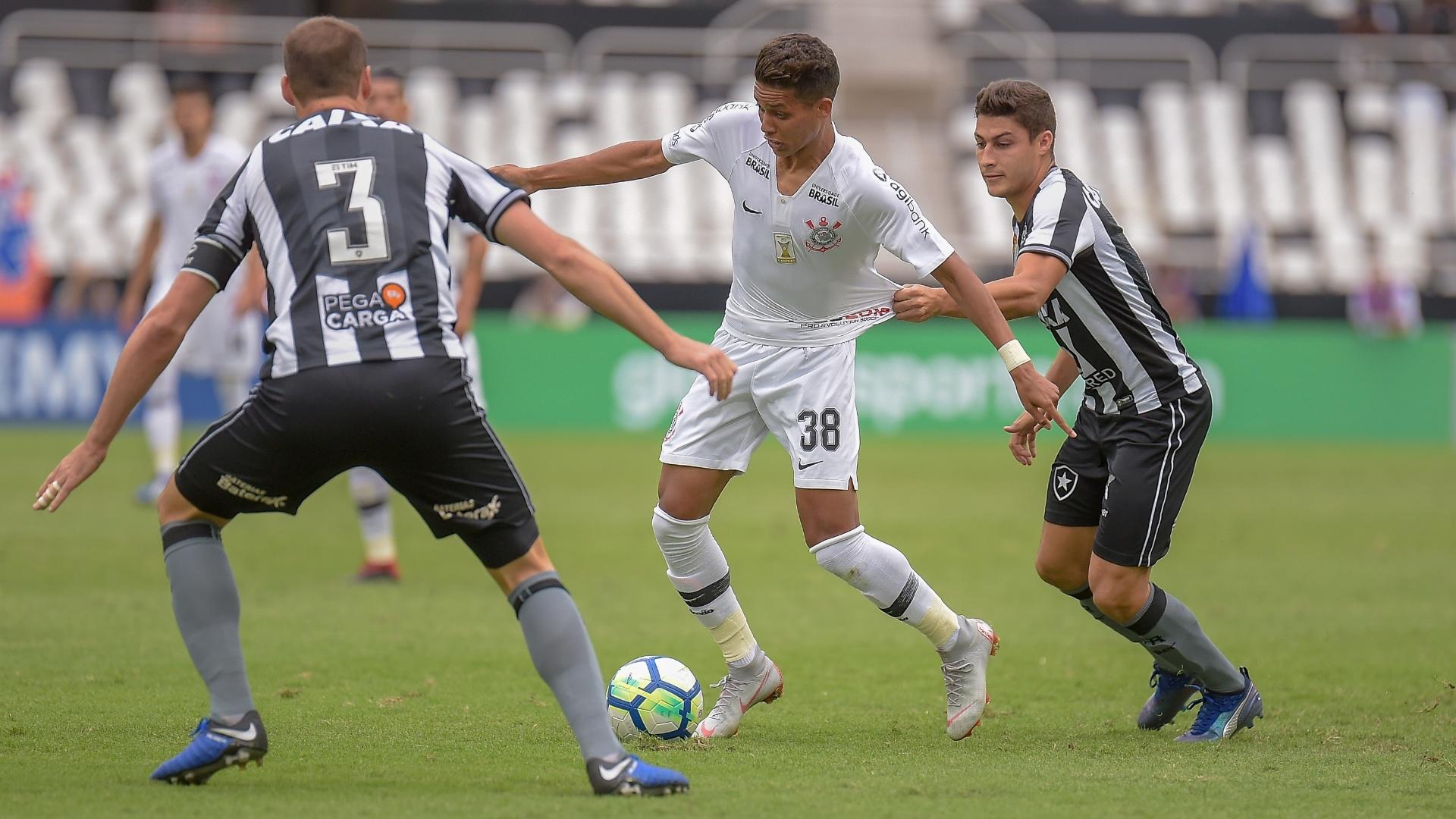 Pedrinho, do Corinthians, tenta a jogada contra Erik e Joel Carli, do Botafogo