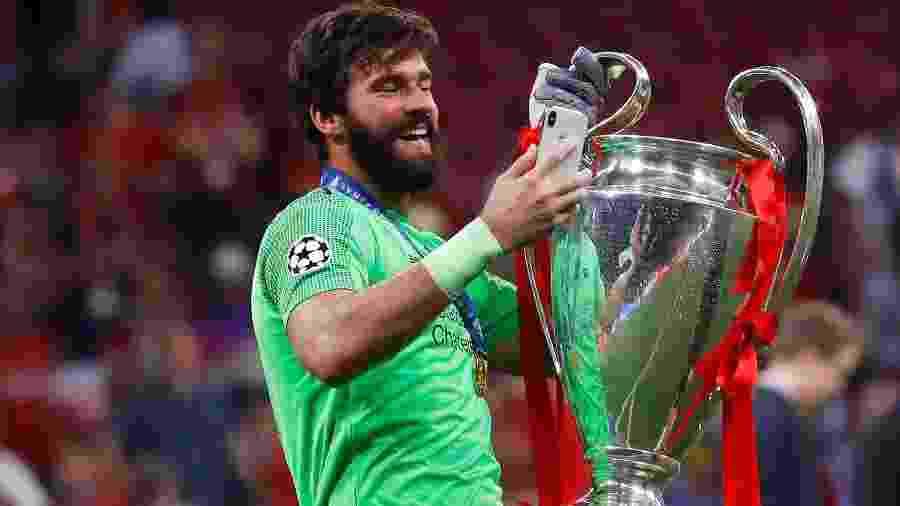 Alisson carrega troféu da Champions League - Kai Pfaffenbach/Reuters