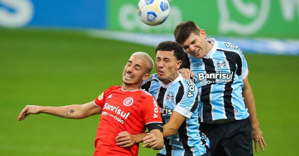 Zagueiro gremista Walter Kannemann disputa bola no alto com o atacante Thiago Galhardo, do Inter, no clássico Gre-Nal 433, pelo Brasileirão
