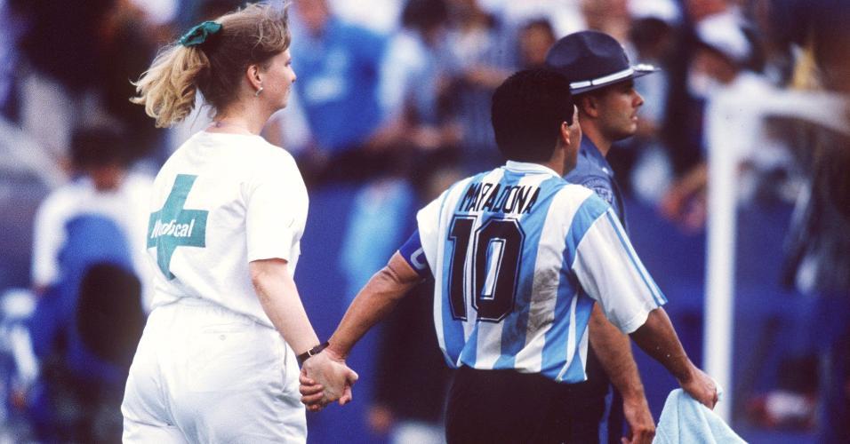 Diego Maradona em campo acompanhando de representante do controle antidoping