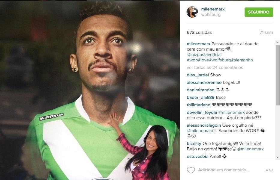 Milene Marx na frente do painel com a imagem do marido, o jogador Luiz Gustavo