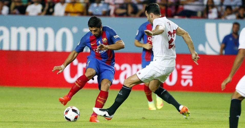 Suárez tenta jogada em partida contra o Sevilla