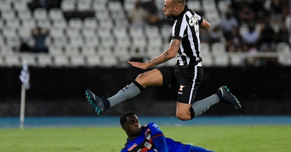 O goleiro Klever evita o ataque de Guilherme na partida entre Botafogo e Atlético-GO, no Nilton Santos