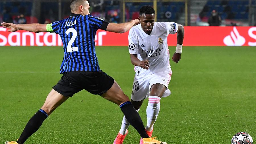 Vinícius Jr disputa a bola com Rafael Tolói em jogo do Real Madrid contra o Atalanta - TIZIANA FABI/AFP