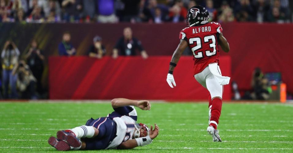 Robert Alford corre para anotar o terceiro touchdown dos Falcons, após interceptar passe de Tom Brady, que tentou pará-lo e ficou no chão
