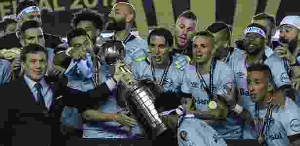 Capitão do Grêmio, o zagueiro Geromel recebe a taça da Libertadores - AFP PHOTO / JUAN MABROMATA