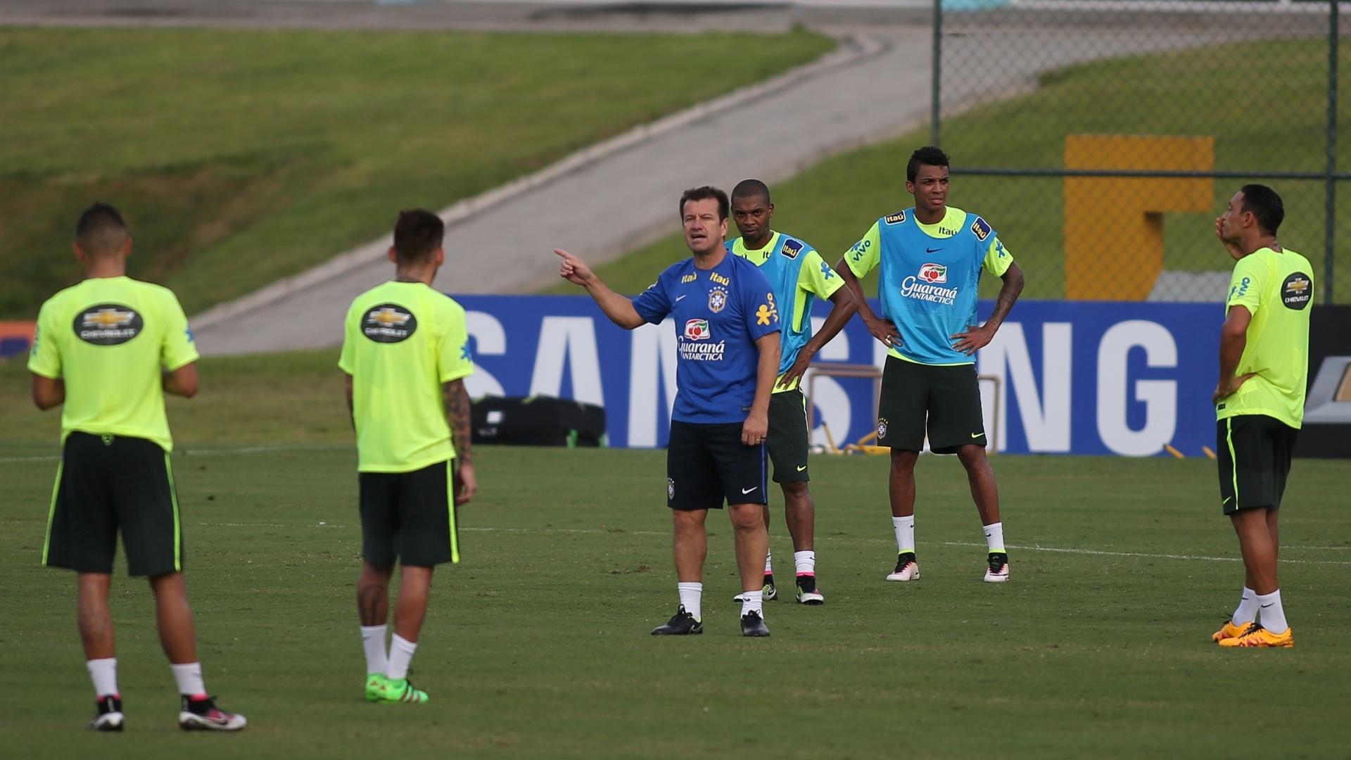 Com Fernandinho com o colete dos titulares ao fundo, Dunga dá instruções em treino