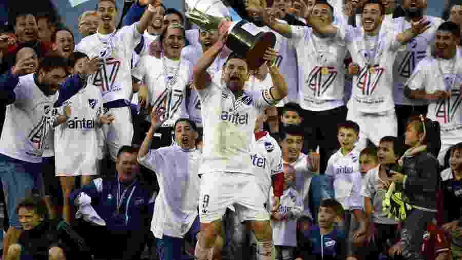 O jogador Gonzalo Bergessio ergue o trófeu do Nacional após conquista do título do Campeonato Uruguaio contra o Peñarol, no Estádio Centenário, em Montevidéu - Xinhua/Nicolás Celaya