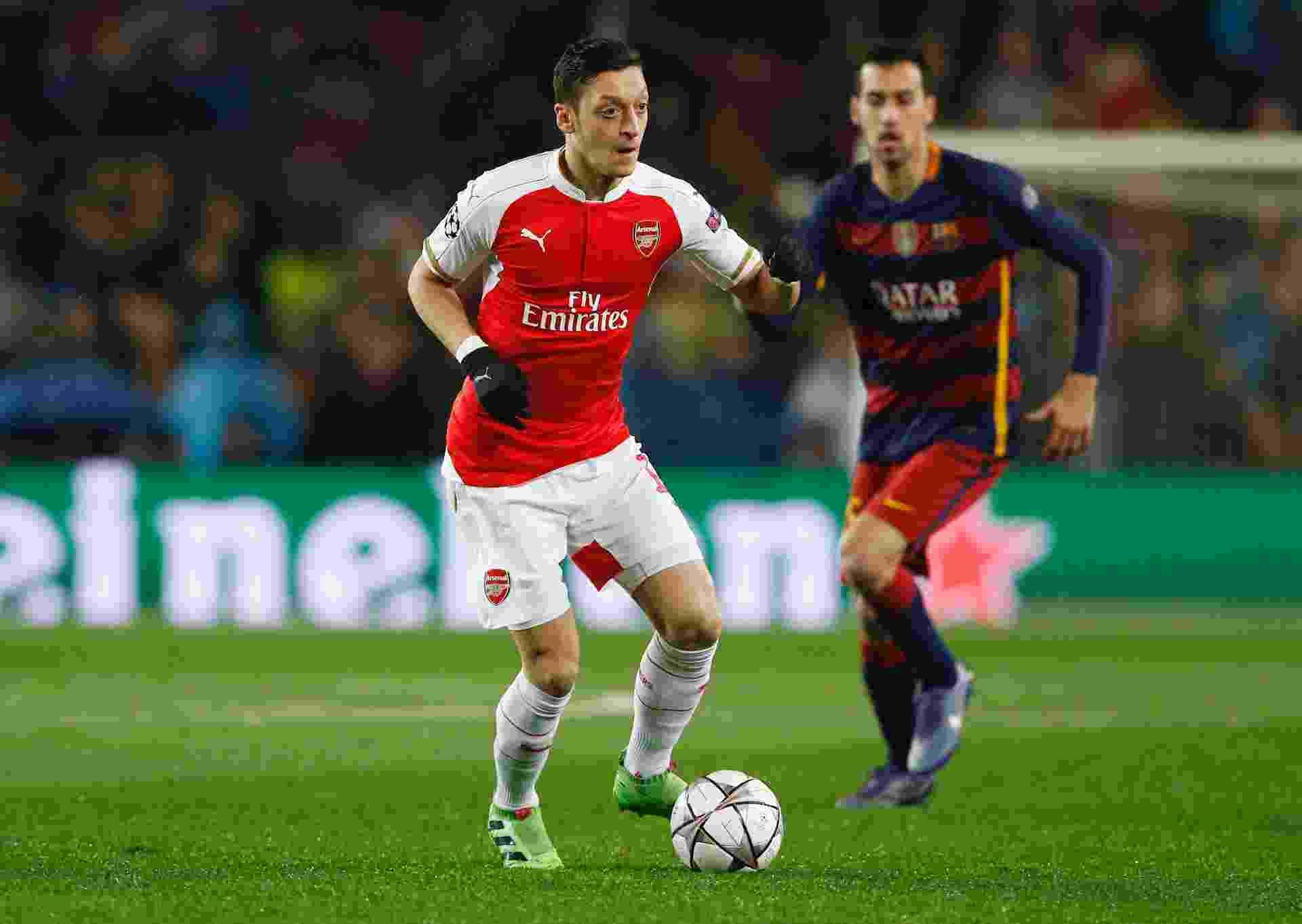 Ozil tenta a jogada acompanhado pela marcação de Busquets na partida entre Barcelona e Arsenal pela Liga dos Campeões - Carl Recine/Reuters