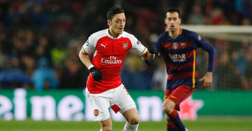 Ozil tenta a jogada acompanhado pela marcação de Busquets na partida entre Barcelona e Arsenal pela Liga dos Campeões