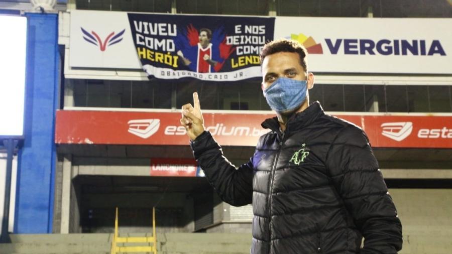 Ex-jogador Neto posa para foto próximo de faixa do Paraná em homenagem a Caio Júnior - Márcio Cunha/ACF