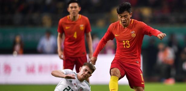 He Chao, da China, de mangas compridas durante amistoso contra País de Gales
