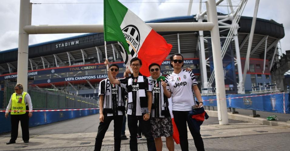 Torcedores da Juventus posam para foto na frente do estádio que receberá a final da Liga dos Campeões em Cardiff