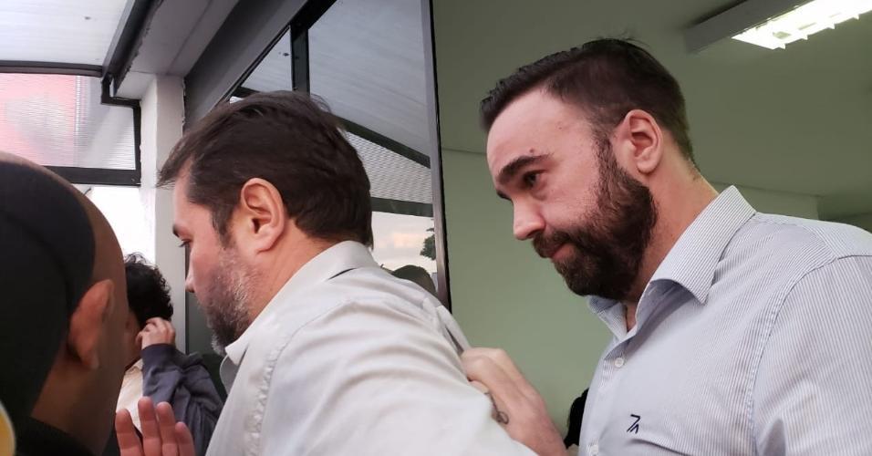 Rodrigo Galo (à direita) deixa a delegacia após prestar depoimento