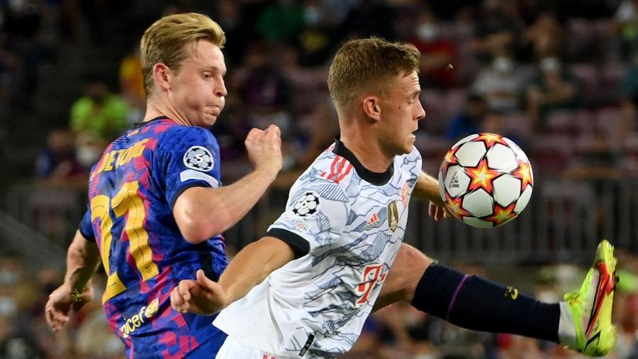 De Jong e Kimmich em disputa durante Barcelona x Bayern de Munique, pela Liga dos Campeões - AFP